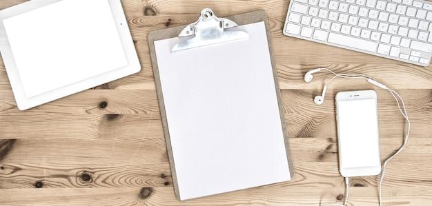 Kantoorwerkplek met klembord, papier, toetsenbord, pad, telefoon, koptelefoon, briefpapier en kantoorbenodigdheden. bedrijfsconcept met ruimte voor uw tekst en afbeelding
