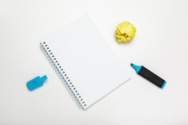 Kantoorwerkruimte met een leeg notitieboekje, verfrommeld papier