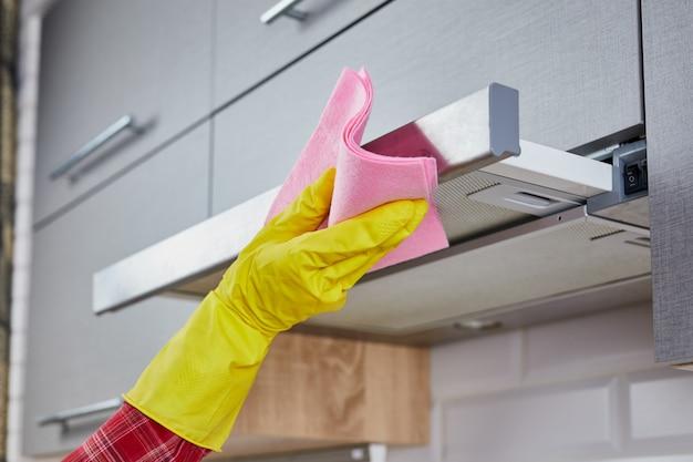 Kap van het vrouwen de schoonmakende kooktoestel met vod in keuken. sluit van wijfje indienen omhoog rubber beschermende gele handschoenen schoon de afzuigkap van het keukenmetaal met vod. huis, huishouden concept
