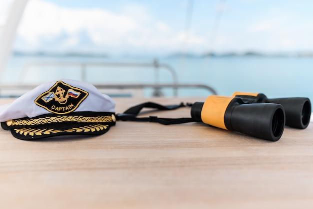 Kapiteinshoed en verrekijker op een jacht