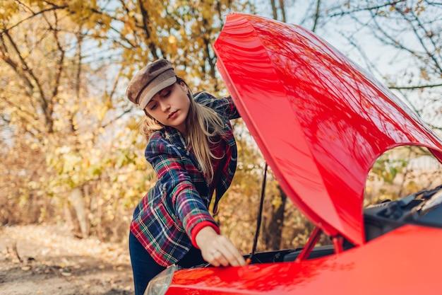 Kapotte auto. droevige vrouw die kap van haar auto opent die in openlucht op bosweg ophield. breken