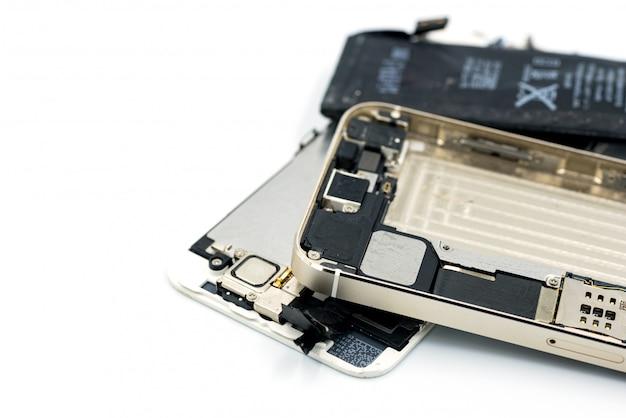 Kapotte telefoon, reserveonderdelen, batterij is leeg, mobiele telefoon op witte achtergrond