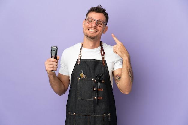 Kapper blanke man in een schort geïsoleerd op paarse achtergrond met een duim omhoog gebaar
