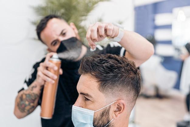 Kapper brengt haarlak aan op het haar van een gemaskerde man die in een kapperszaak zit