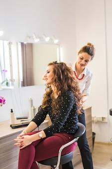 Kapper coiffeur maakt kapsel voor jonge vrouw