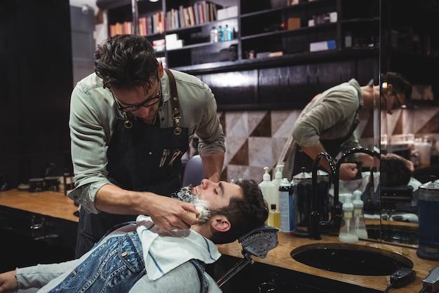 Kapper crème toe te passen op de baard van de klant