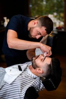 Kapper die de baard van een man in orde maakt