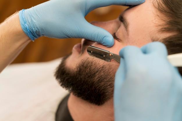 Kapper die de baard van een mannelijke klant scheren en contouren geeft