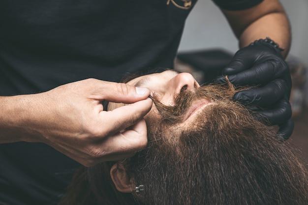 Kapper die de snor van een man snijdt.