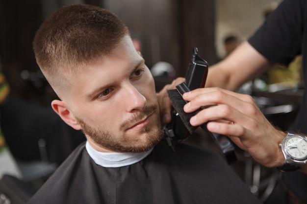 Kapper die een cliënt scheert bij de salon