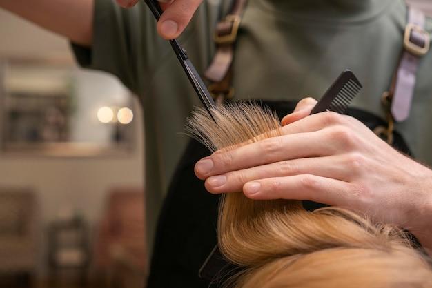 Kapper die het haar van een klant binnenshuis verzorgt