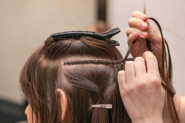 Kapper die het haar van een klant in de salon stylt