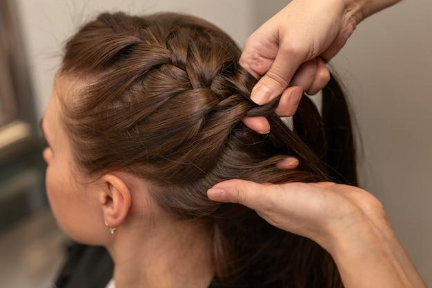 Kapper die het haar van een klant in de salon verzorgt