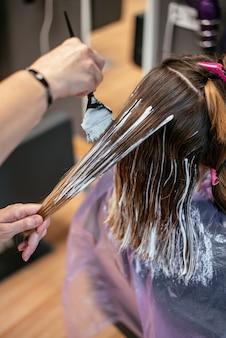 Kapper die het haar van een vrouw verft