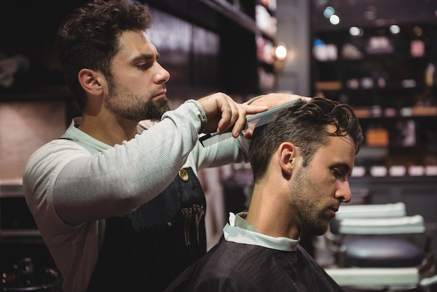 Kapper die het haar van klanten kamt