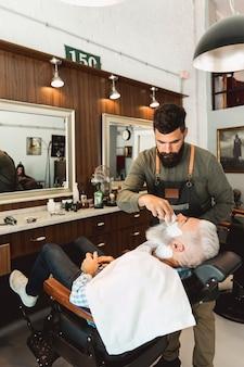 Kapper die scheerschuim toepassen op de oude mens in haarsalon