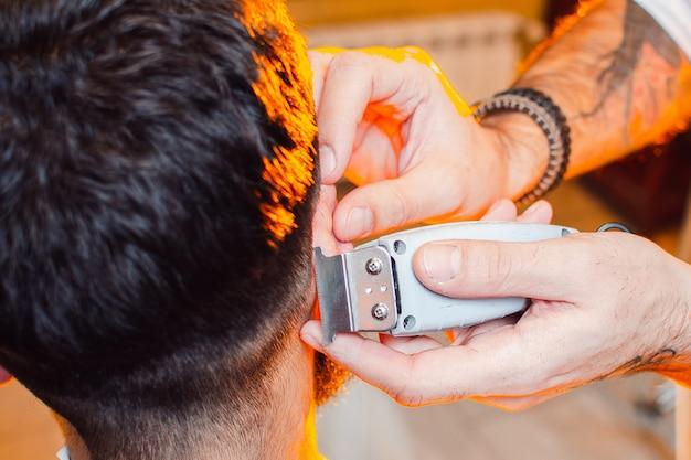 Kapper doet een knipbeurt op zijn hoofd met een trimmer voor een jonge knappe kerel met een snor en baard