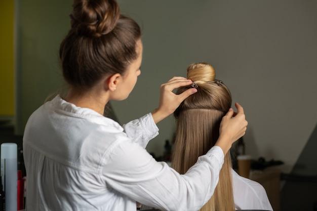 Kapper doet haarstyling aan een langharige blonde vrouw in een schoonheidssalon