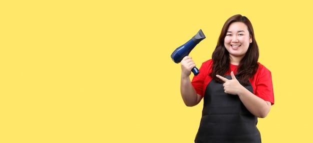 Kapper drogen haar in een schoonheidssalon geïsoleerd op gele achtergrond in studio met kopie ruimte.