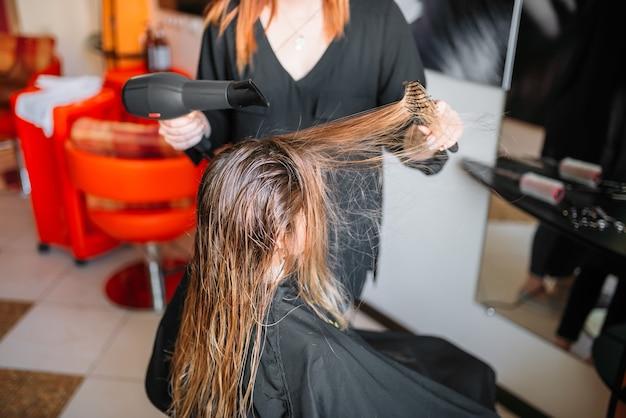 Kapper drogen haar met een droger, vrouwelijke hairdress in kapsalon. kapsel maken in schoonheidssalon