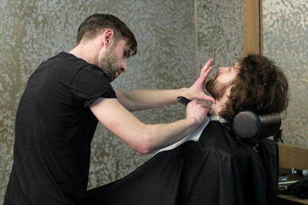 Kapper. een kapper scheert de baard van de mens met de machine