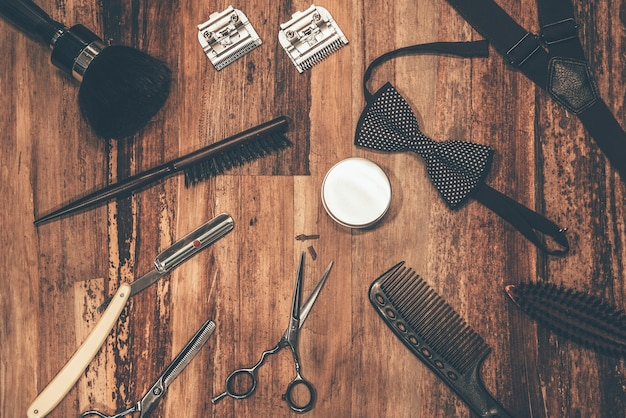 Kapper gereedschap. bovenaanzicht van kappersgereedschap en accessoires voor mannen liggend op de houtnerf