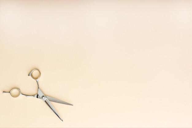 Kapper gereedschap. kappersschaar op beige kleur achtergrond met kopie ruimte voor tekst. kappersservice. schoonheidssalon service