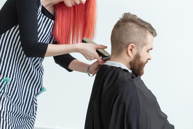 Kapper, haarstylist en kapper winkelconcept - vrouw haarstylist snijden een bebaarde man.