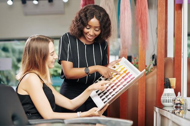 Kapper helpt klant bij het kiezen van een nieuwe haarkleur