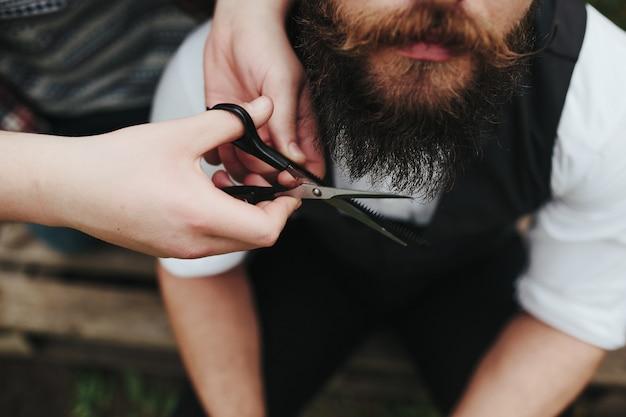 Kapper het snijden van een baard met een schaar