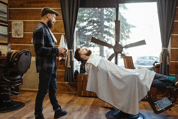Kapper in hoed en bebaarde klant, baard knippen. professionele kapperszaak is een trendy beroep