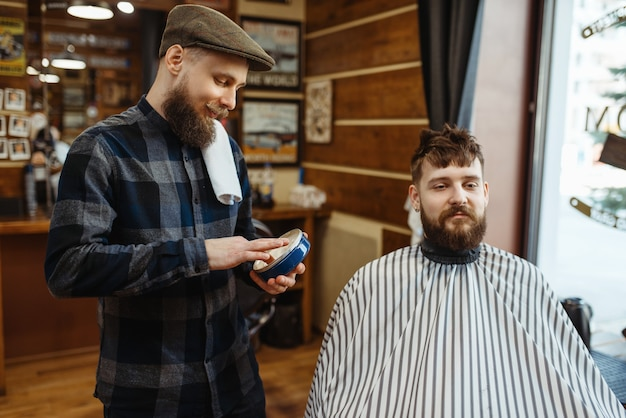 Kapper in hoed en bebaarde klant. professionele kapperszaak is een trendy beroep