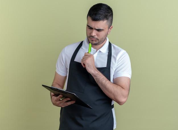 Kapper in schort met klembord en pen die ernaar kijkt met een serieus gezicht over een groene achtergrond
