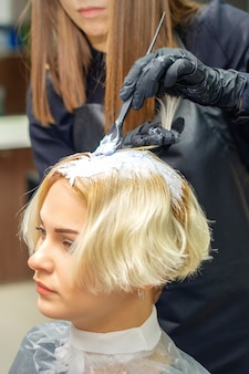 Kapper in zwarte handschoenen verft haar van jonge vrouw in witte kleur in de kapsalon