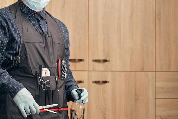 Kapper, kapper in een schort met handschoenen en een medisch masker op een lichte achtergrond