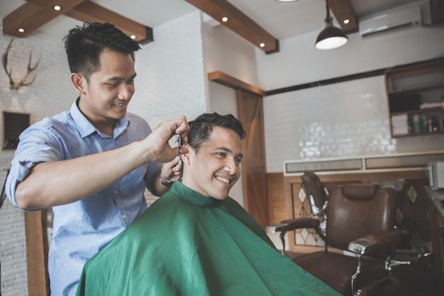 Kapper kapsel maken voor een aantrekkelijke man in de kapsalon