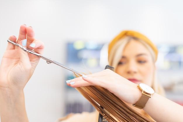 Kapper knipt haar met een schaar naar een blanke klant in haar kapper cselectieve focus