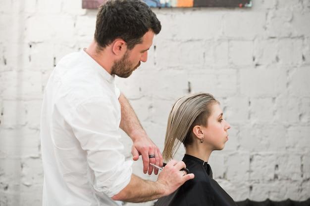 Kapper knipt haar met een schaar op de kroon van knappe tevreden klant in professionele kapsalon