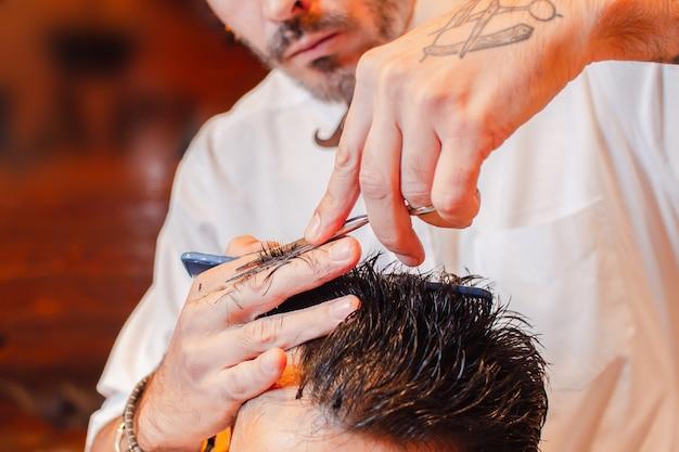 Kapper knipt het haar op haar hoofd met een schaar. kapsel close-up. kapperszaak