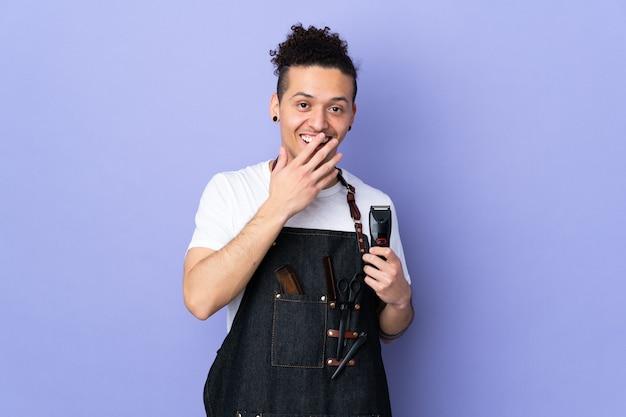Kapper man in een schort over geïsoleerde paarse achtergrond met verrassende gelaatsuitdrukking
