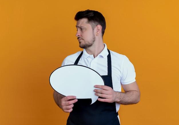 Kapper man in schort bedrijf leeg tekstballon teken opzij kijken ontevreden staande over oranje muur