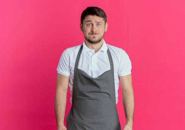 Kapper man in schort camera kijken verward waait wangen staande over roze achtergrond