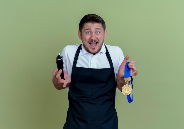 Kapper man in schort houden baard trimmer en gouden medaille kijken camera opgewonden en gelukkig staande over groene achtergrond