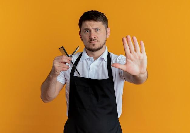 Kapper man in schort houden schaar en kam stoppen zingen met open hand kijken camera met ernstig gezicht staande over oranje achtergrond