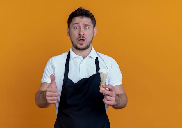 Kapper man in schort houden scheerkwast duimen opdagen kijken camera verward en verrast staande over oranje achtergrond