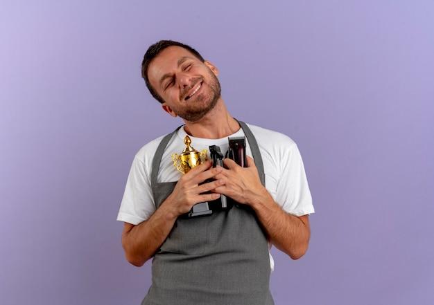 Kapper man in schort houden trofee en haar snijmachine glimlachend dankbaar gevoel met gesloten ogen staande over paarse muur