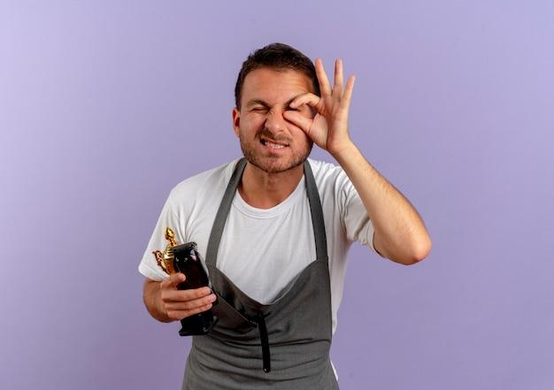 Kapper man in schort met haar snijmachine op zoek ok teken in de buurt van zijn oog staande over paarse muur