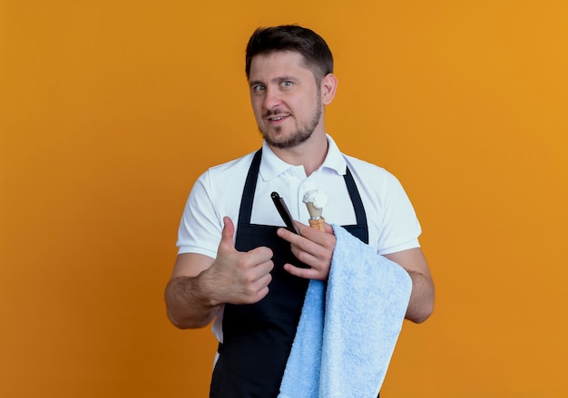 Kapper man in schort met handdoek aan zijn hand met scheerkwast met schuim en scheermes glimlachend tonen duimen omhoog staande over oranje muur
