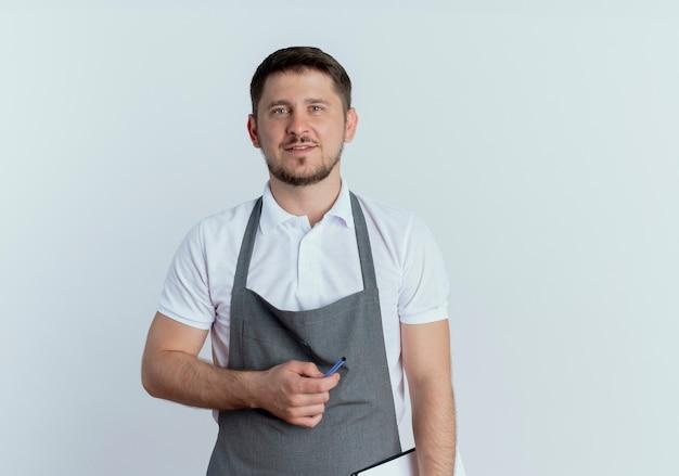 Kapper man in schort met klembord en pen met glimlach op gezicht staande over witte muur