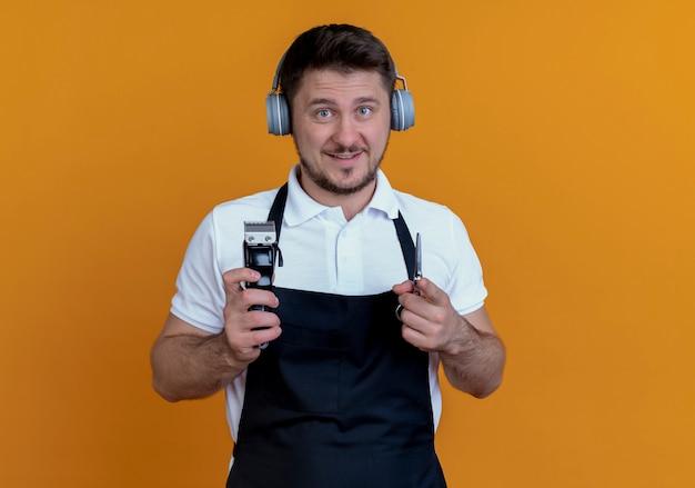 Kapper man in schort met koptelefoon houden baard trimmer en schaar kijken camera met glimlach op gezicht staande over oranje achtergrond